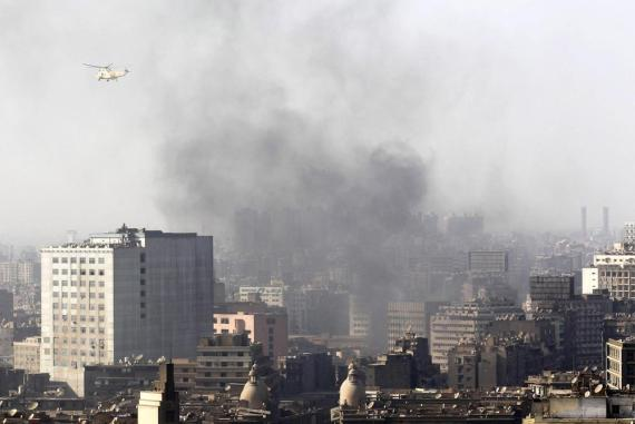 A military helicopter flies over clouds of smoke in Cairo Square in Cairo.