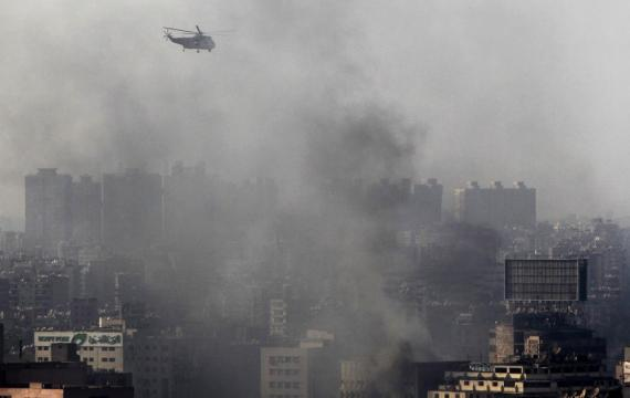 A military helicopter flies over clouds of smoke near Ramses Square in Cairo
