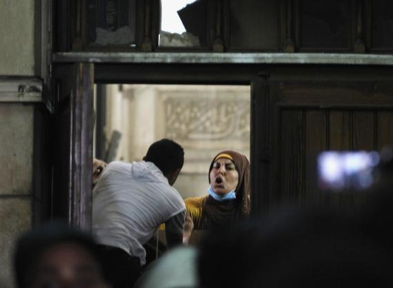 An anti-coup protesters talks to police from behind a barricade inside the Fateh mosque.