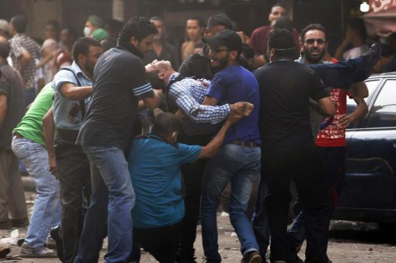 Protesters carry an injured demonstrator at Ramses Square in Cairo.