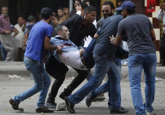 Protesters carry an injured demonstrator during clashes at Ramses Square in Cairo.