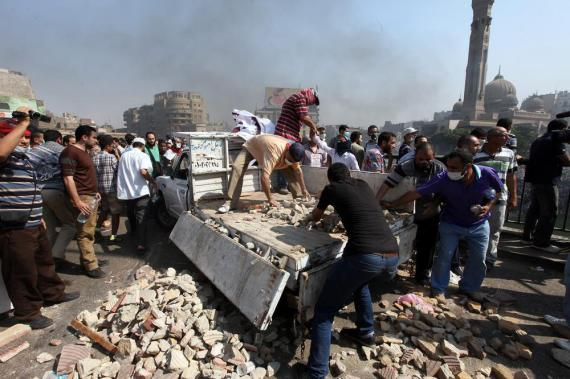 Protesters collect stones to throw at security forces during clashes near Ramses square in Cairo.