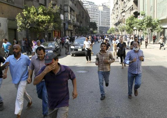 Supporters of the deposed Egyptian president Mohamed Morsi run away from tear gas during clashes outside Al-Fath mosque in Ramses square.